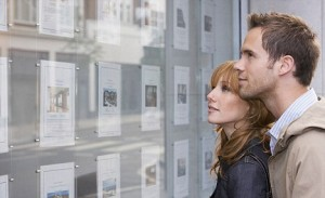 AG2JDY Couple looking in window outside estate agents. Image shot 2007. Exact date unknown.
